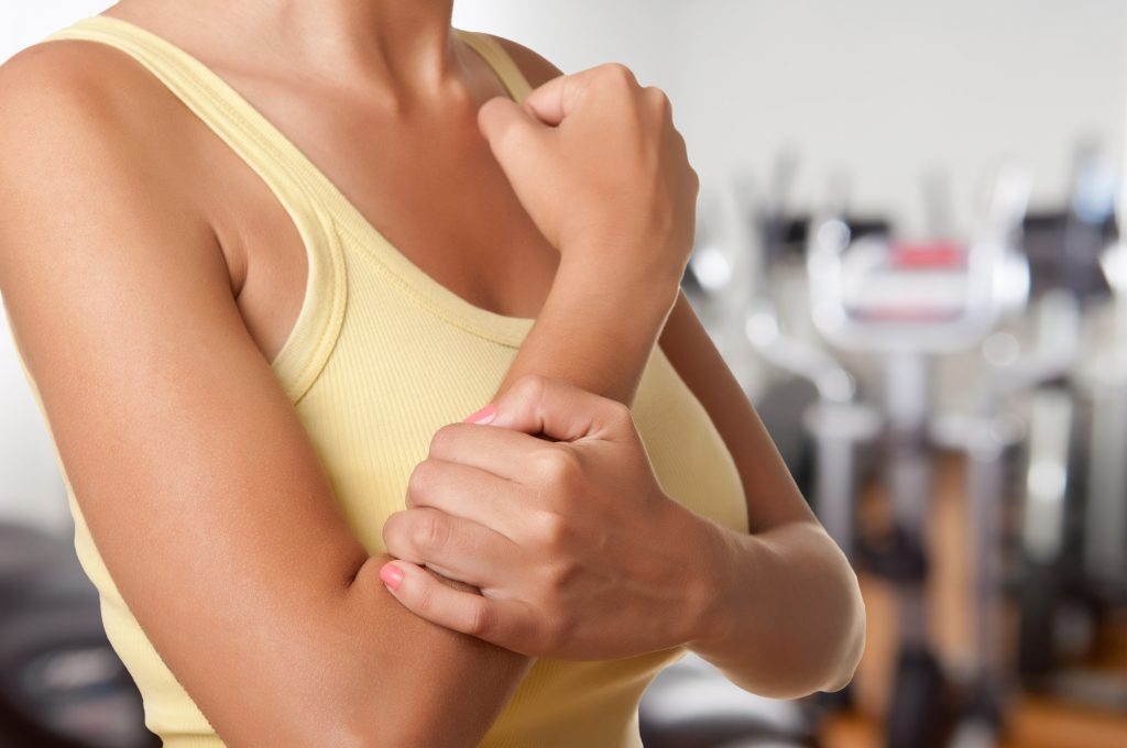 Female with pain in her forearm in a gym