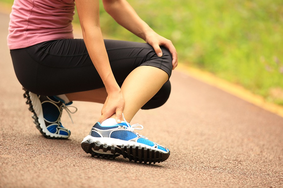 woman runner hold her twisted ankle